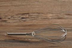 Egg beater. Whisk,  on a wooden background Stock Images