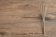 Egg beater,. Whisk,  on a wooden background Royalty Free Stock Images