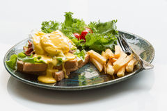 Egg Benedict with french fries. On white Royalty Free Stock Image