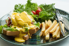 Egg Benedict. Serve with french fries Royalty Free Stock Image