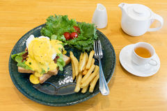 Egg Benedict. Serve with french fries and hot tea Royalty Free Stock Image