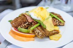 Egg Benedict with seven grain bread with sliced of orange and asparagus at restaurant in Dubai Royalty Free Stock Photo
