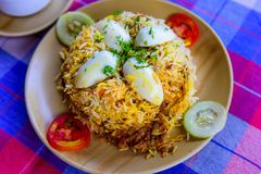 Egg Biryani - Basmati rice cooked with masala, eggs and spices, overhead view, close up. Egg Pilaf or Pulao served with vegetables. And yogurt royalty free stock image