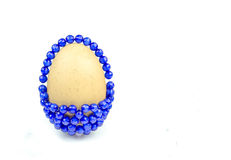 Egg with blue beads on background Stock Images