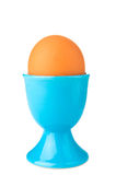 Egg in blue egg cup isolated on white Stock Photos