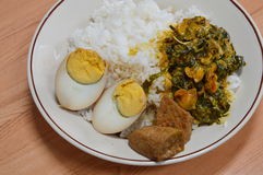 Egg boiled in brown sauce and cockle curry with betel leaves on rice Stock Image