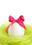 Egg with bow is in the nest of sisal fibre Royalty Free Stock Photography