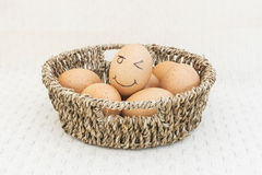 Egg in a brown Basket. And happy egg stock photo