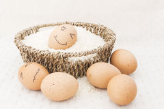 Egg in a brown Basket raw rice. And happy egg royalty free stock images
