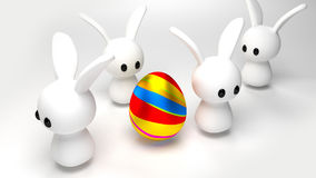 Egg and Bunnies. Some toy bunnies around an easter egg Royalty Free Illustration