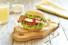 Egg burger with vegetables and fried bacon Royalty Free Stock Images
