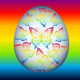 Egg with butterflies of rainbow color on a rainbow background Royalty Free Stock Photo