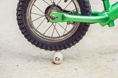 Egg - calcium, under the heavy wheel of a bicycle does not break. The power of the calculus concept royalty free stock photography