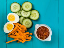 Egg Carrot and Cucumber Crudites With Tomato Salsa. Against a Blue Background Stock Photo