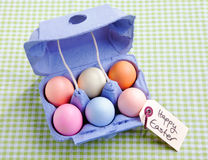 Egg carton with different colored Eggs. On a green checked background with a handwritten memo Happy Easter Royalty Free Stock Images