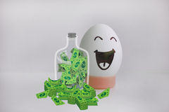 Egg cheerful with a face alone anecdote. Concept of profit and safety of the deposit. Dollars in bundles and a glass jar with currency. Egg cheerful with a face Royalty Free Stock Images