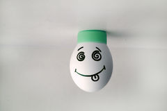 Egg cheerful with face stand on head. Royalty Free Stock Photography