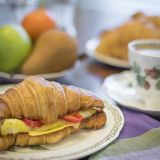 Egg and cheese croissant with fruit and coffee Royalty Free Stock Images