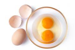 Egg com gemas em uma bacia de vidro e em shell de ovo, sobre o backgr branco fotos de stock