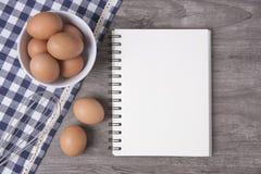 Egg con il libro aperto di ricetta sulla tavola di legno fotografie stock