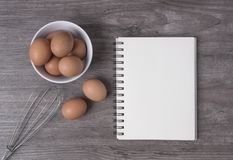 Egg con il libro aperto di ricetta sulla tavola di legno, immagini stock libere da diritti
