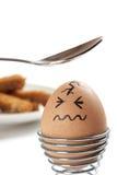 Egg con la cara exhausta, para ser golpeado alrededor con la cucharilla Foto de archivo libre de regalías
