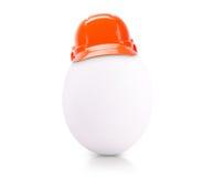 Egg in construction helmet isolated on white Stock Images