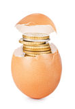 Egg cracked open with gold coins coming out against. A white background Royalty Free Stock Image