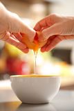 Egg cracking. Food preparing, back view of hands cracking up a raw egg Stock Photo