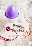 Egg Cup With Purple Easter Egg. Purple egg in an egg cup with a Happy Easter tag Royalty Free Stock Image