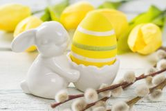 Egg cup with a yellow easter egg and tulips Stock Images