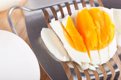 Egg cutter and cutted eggs on wooden table Stock Photos