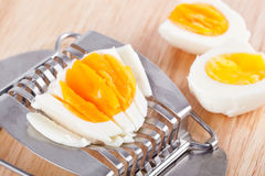 Egg cutter and cutted eggs on wooden table Royalty Free Stock Photo