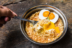 Egg cutter by fork and spicy noodle on the table. Stock Photography