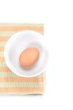 Egg dans la cuvette sur le napery de couleur, sur le fond blanc Images stock