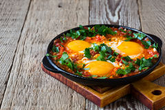 Egg dish with tomato sauce served in cast iron pan, shakshouka. Homemade egg dish with tomato sauce served in cast iron pan, shakshouka, comfort food royalty free stock image
