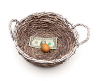 Egg and dollar in a basket on a white background Royalty Free Stock Images