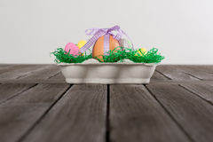 Egg in a easter nest with small eggs on a table. Royalty Free Stock Photography
