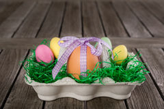 Egg in a easter nest with small eggs on a table. Stock Image