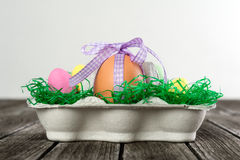 Egg in a easter nest with small eggs on a table. Royalty Free Stock Image