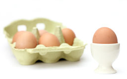 Egg with egg cup and eggs in a package. On white background royalty free stock photo