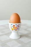 Egg in egg holder. One hard boiled egg in an egg holder on a table Royalty Free Stock Photo