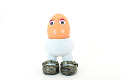 Egg in eggcup. Egg in cup with silver shoes front view isolated Royalty Free Stock Photos