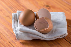 Egg and eggshells on the kitchen dishtowel with natural moody backlight Royalty Free Stock Photography