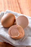 Egg and eggshells on the kitchen dishtowel with natural moody backlight Stock Image
