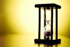 Egg el contador de tiempo o el reloj de arena en un fondo amarillo Fotografía de archivo