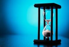 Egg el contador de tiempo o el reloj de arena en un fondo azul Imágenes de archivo libres de regalías