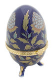 Egg faberge. Ceramic casket as eggs faberge dark blue color with gold furnish it is isolated on a white background Stock Images