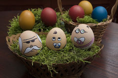 Egg face family in wicker basket. Easter  egg face family in wicker basket, grandfather and two grandson Royalty Free Stock Image