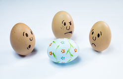 Egg faces and an easter egg Royalty Free Stock Image